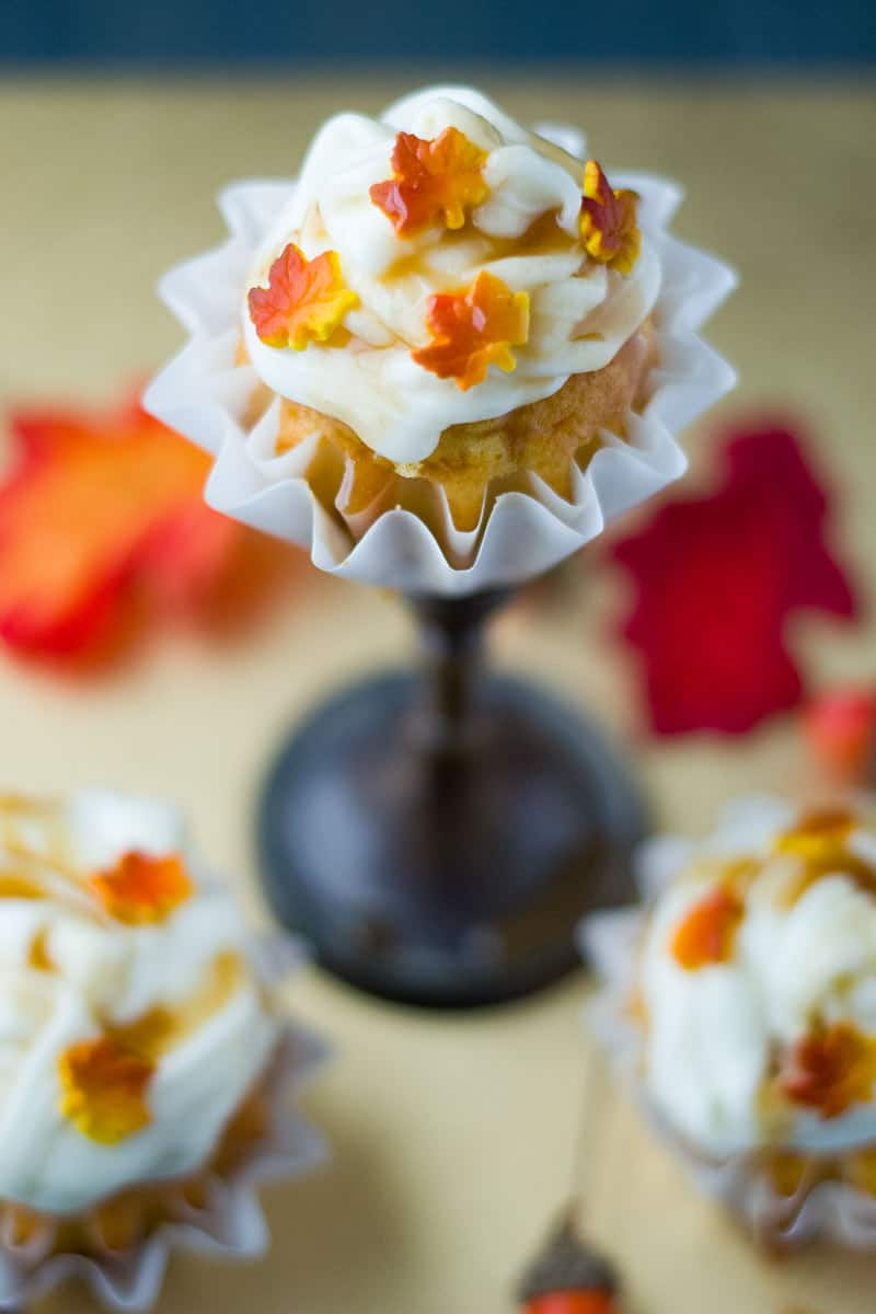 Thanksgiving Carrot Cupcakes - Close up of one Thanksgiving themed carrot cupcake with white frosting and fall candy leaves