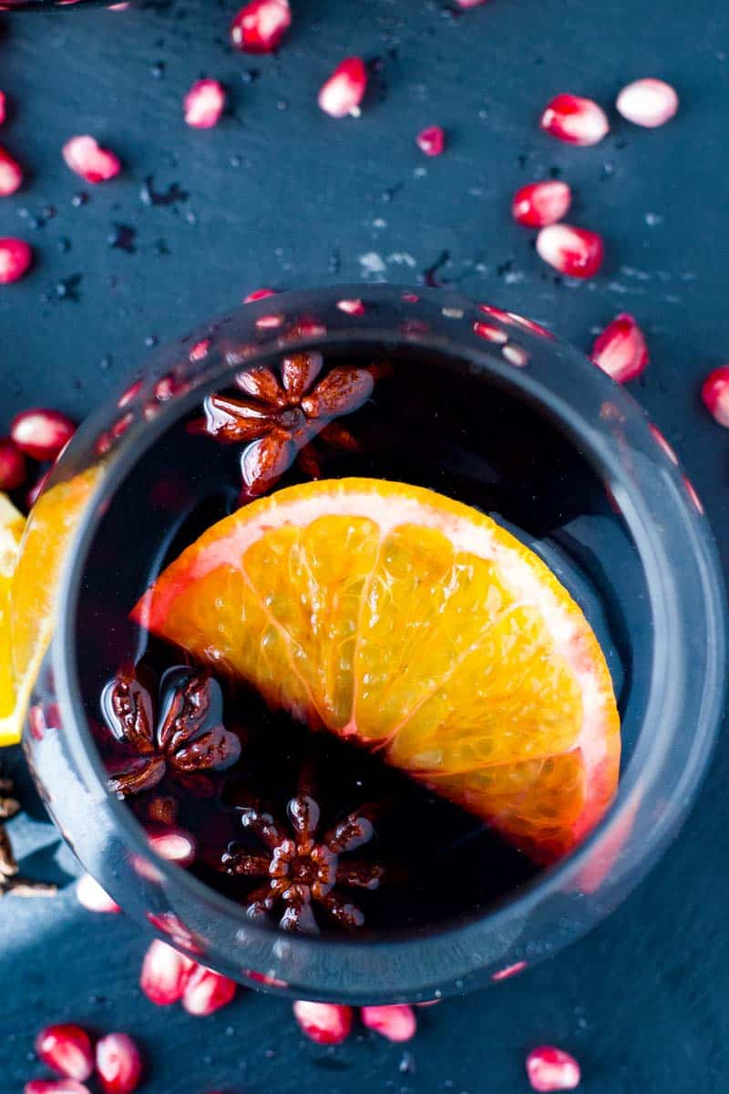 Slow Cooker Spiced Mulled Wine with Pomegranates and Oranges. Floating star anise and cinnamon.