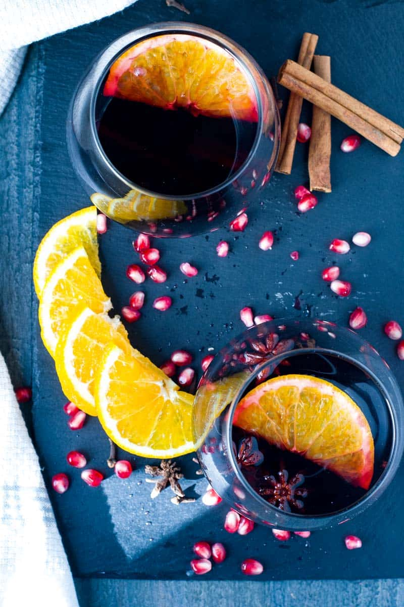 Slow Cooker Spiced Mulled Wine with Pomegranates and Oranges. Sliced oranges and pomegranate seeds.