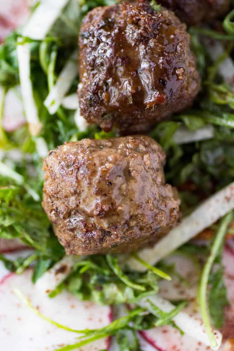 Two Keto Meatballs on a bed of arugula and jicama