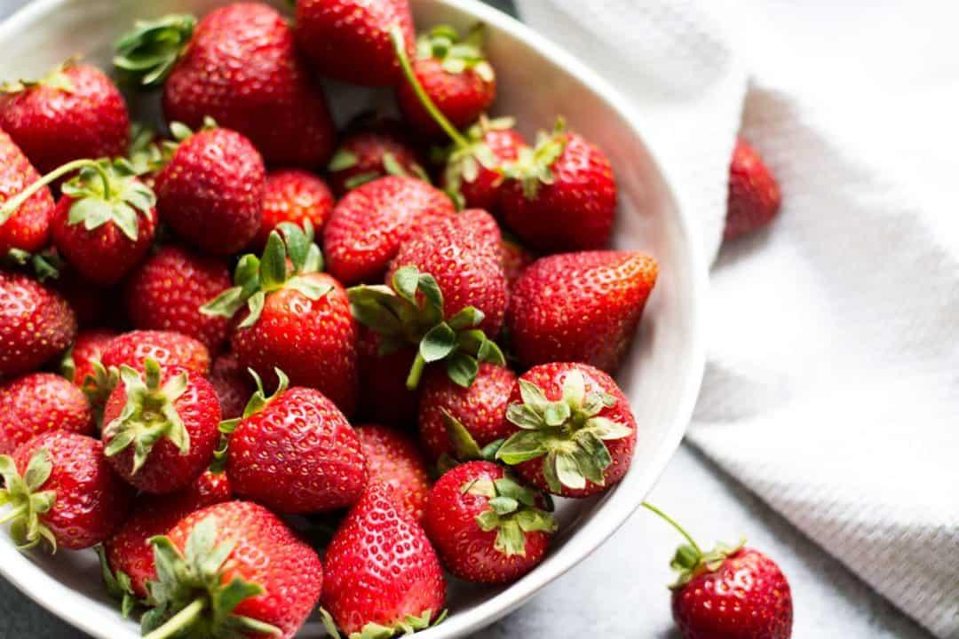 big white bowl of fresh strawberries