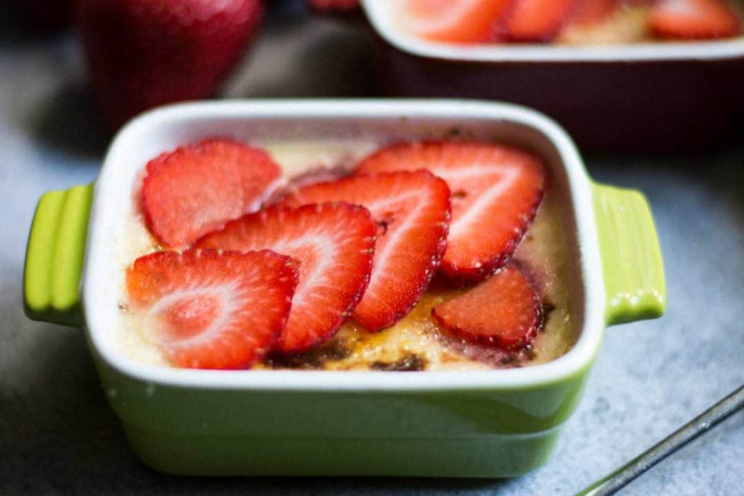 close up of one green ramekin with layer of strawberries