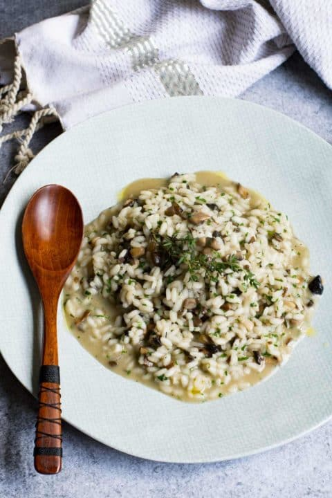 Overhead shot of vegan mushroom risotto on a light blue patterned plate with wooden spoon.
